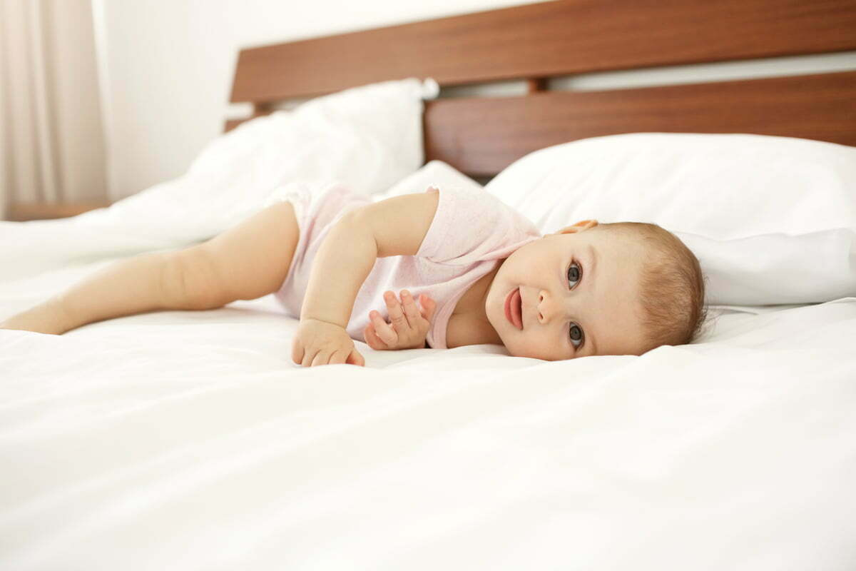 Portrait of beautiful cute newborn baby looking at camera showing tongue lying on bed at home.